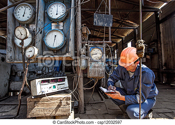 Worker on a gas well collecting data from sensors and special devices - csp12032597