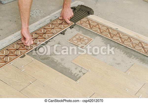 Worker Putting Tiles On The Floor It Installs Strips