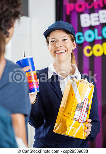 Worker selling snacks to man at cinema concession stand.... stock ...