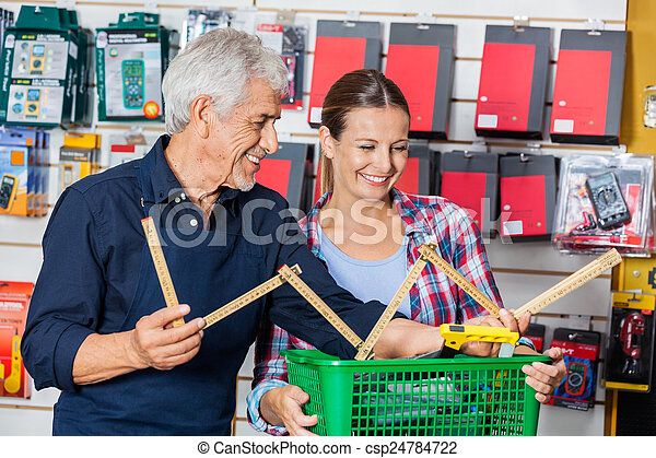 Worker Showing Folding Ruler To Customer In Hardware Shop - csp24784722