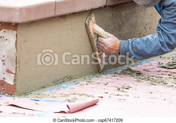 Worker Smoothing Cement with Wooden Float At Construction Site - csp67417209