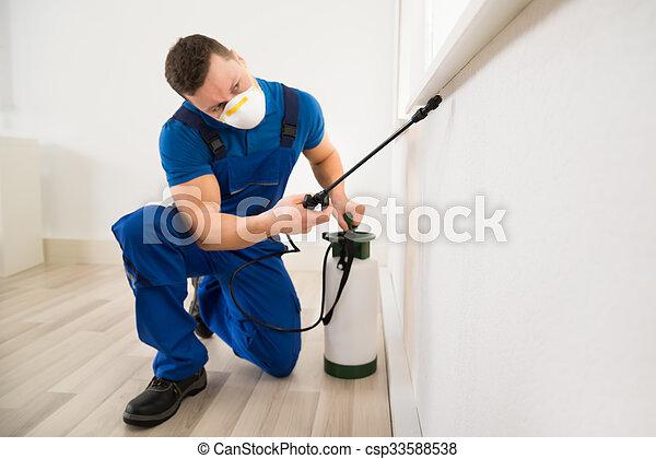 Worker Spraying Pesticide On Window Corner - csp33588538