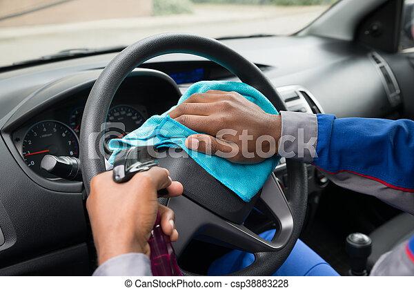 Worker Wiping Steering Wheel In Car - csp38883228
