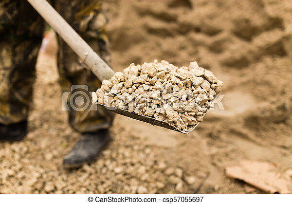 worker with a shovel at the construction site - csp57055697