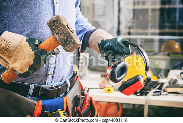 Worker with a tool belt and a hammer - csp44081118