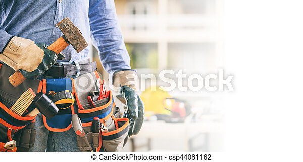 Worker with a tool belt and a hammer - csp44081162