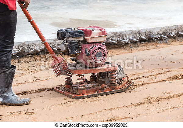 Worker with red soil compactors in construction site - csp39952023