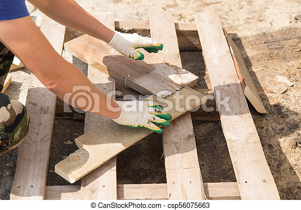 worker working with wooden planks at construction site - csp56075663