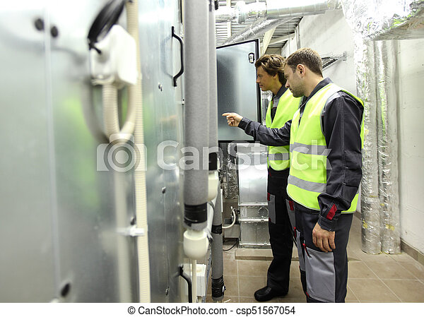Workers in electrical switchgear room - csp51567054