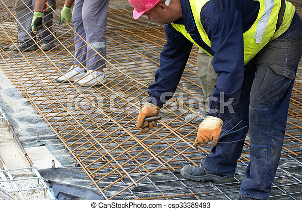 Workers installing reinforcement mesh - csp33389493