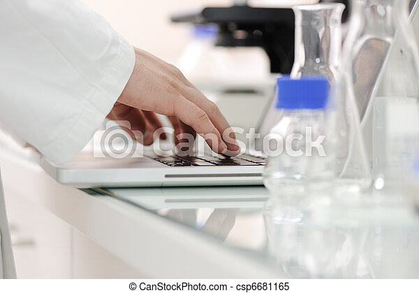 Working in lab with liquids and writing results on laptop, closeup - csp6681165