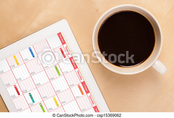 Workplace with tablet pc showing calendar and a cup of coffee on a wooden work table close-up - csp15369062
