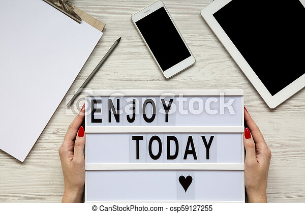 Workplace with tablet, smartphone, notepad and 'Enjoy today' word on lightbox over white wooden background, top view. Female hands hold lightbox. From above, flat-lay, overhead. - csp59127255