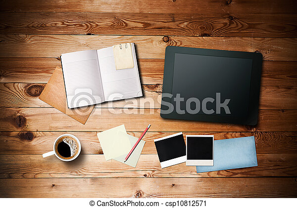 Workspace with coffee cup, tablet pc, instant photos, note paper and notebook on old wooden table - csp10812571