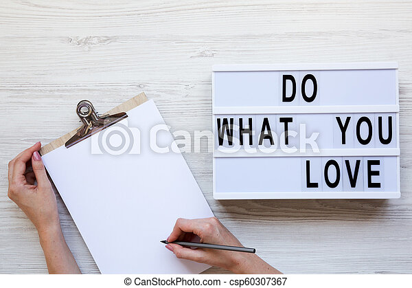 Workspace with female hands, clipboard and 'Do what you love' word on lightbox over white wooden background, top view. From above, flat-lay, overhead. - csp60307367