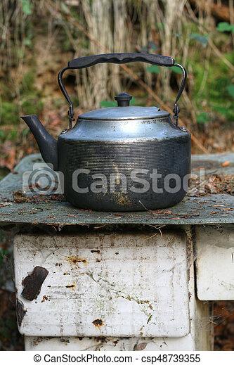 Worn teapot on old stove - csp48739355
