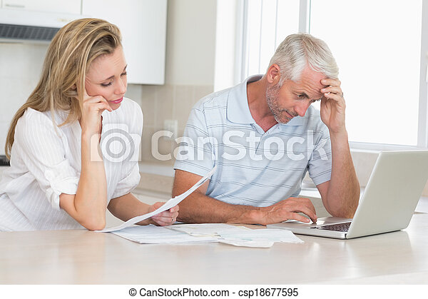 Worried couple working out their finances with laptop - csp18677595