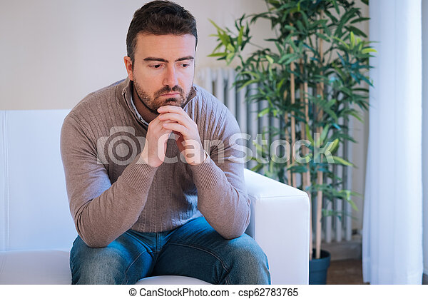 Worried man feeling negative emotions at home - csp62783765