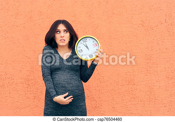 Worried Pregnant Woman Holding a Clock Awaiting her Baby - csp76504460