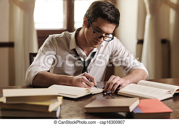 Writer at work. Handsome young writer sitting at the table and writing something in his sketchpad - csp16300907