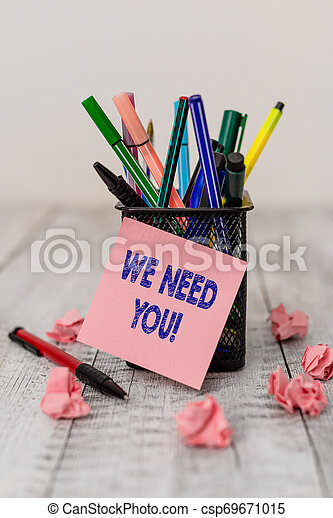 Writing note showing We Need You. Business photo showcasing asking someone to work together for certain job or target Writing equipment and paper scraps with blank sheets on the wooden desk. - csp69671015
