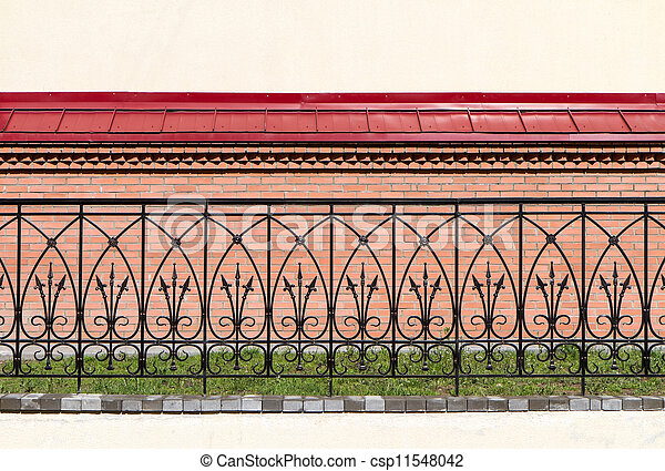 Ornate wrought iron fence against a brick wall stock photo Search