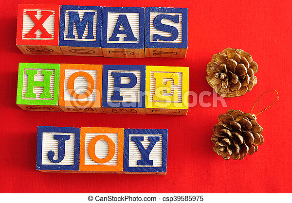 Xmas, Hope and Joy spelled with Alphabet blocks and two acorns on a red background - csp39585975