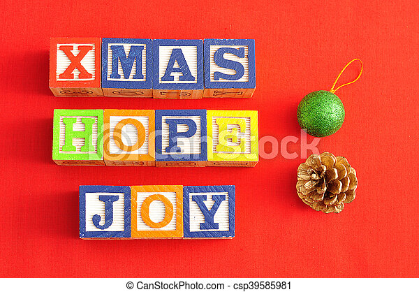 Xmas, Hope and Joy spelled with Alphabet blocks and an acorn and bauble on a red background - csp39585981