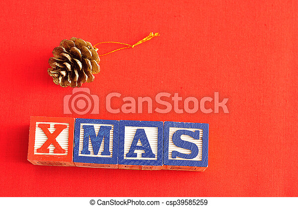 Xmas spelled with Alphabet blocks and an acorn christmas tree decoration on a red background - csp39585259