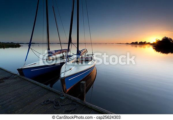 yacht on lake harbor at sunrise - csp25624303