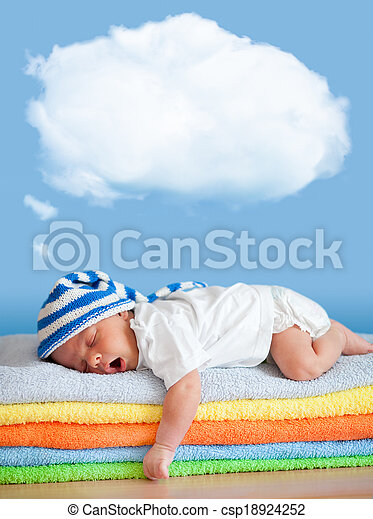 Yawning sleeping baby in funny hat with dream cloud for image or text - csp18924252