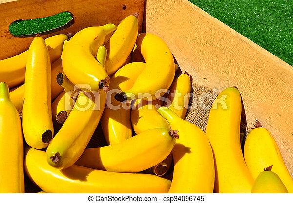 Yellow bananas in a wooden box - csp34096745