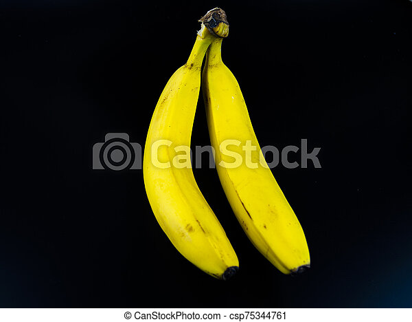 Yellow bananas on a black background. - csp75344761