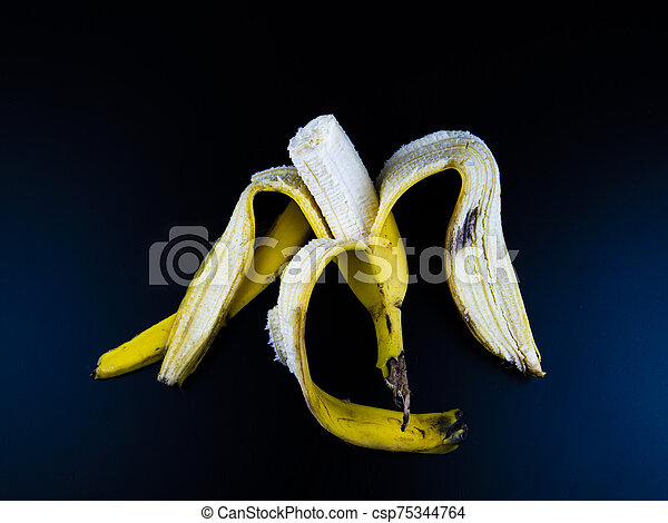 Yellow bananas on a black background. - csp75344764