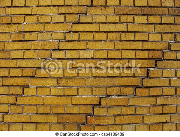 yellow brick wall with 2 large cracks - csp4109489