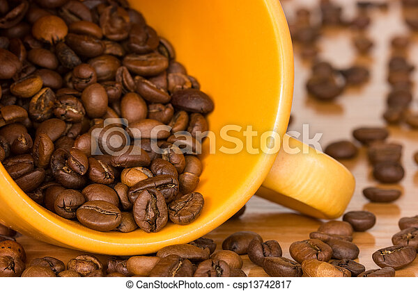 Yellow cup with many coffee beans - csp13742817
