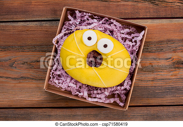 Yellow donut in box, top view. - csp71580419