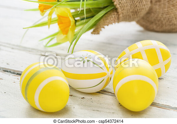 Yellow easter eggs on a wooden background with daffodils - csp54372414