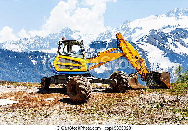 Yellow excavator working near mountains - csp19833320