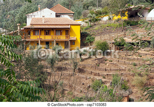 Yellow farm house on a hill surrounded by trees - csp7103083