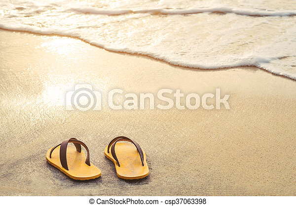 Yellow flip flop on the beach - csp37063398