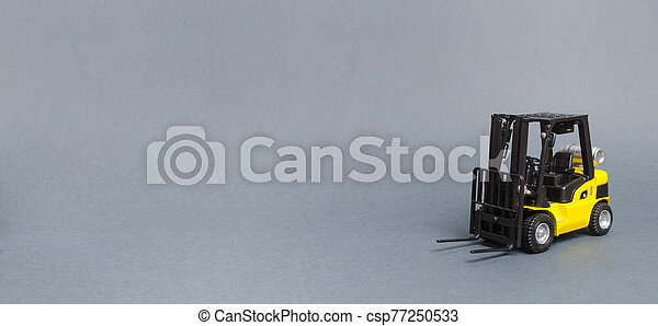 Yellow forklift truck on gray background. Warehouse equipment, vehicle. Logistics and transport infrastructure, industry and agriculture. Unloading, transportation, sorting. Banner, copy space - csp77250533