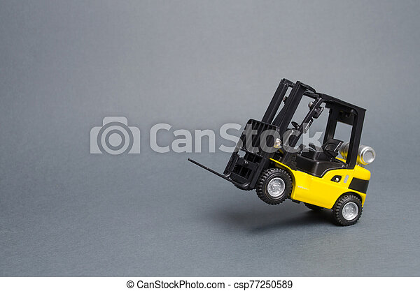 Yellow forklift truck rides on the rear wheels on gray background. Warehouse equipment, vehicle. Logistics and transport infrastructure, industry and agriculture. Unloading, transportation, sorting - csp77250589