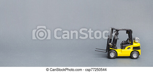 Yellow forklift truck side view on gray background. Warehouse equipment, vehicle. Unloading, transportation, loading cargo. Logistics and transport, industry and agriculture. Banner, copy space - csp77250544