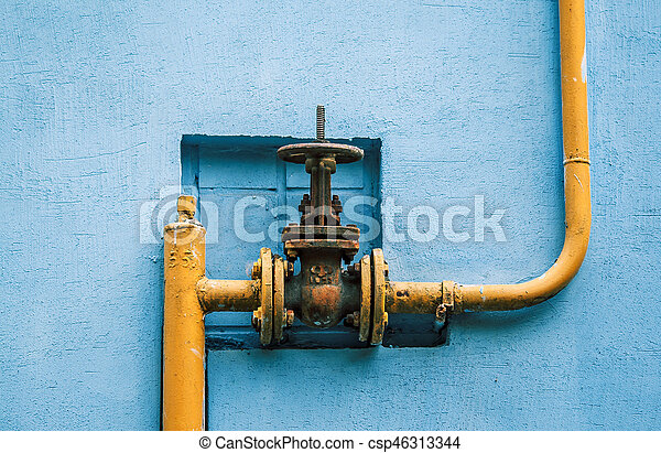 yellow gas pipe with a valve on the blue wall - csp46313344