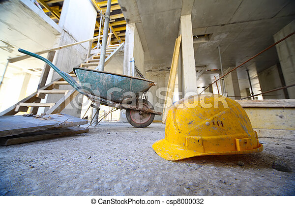Yellow hard hats and small cart on concrete floor inside unfinished building - csp8000032