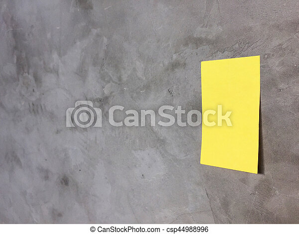 Yellow paper note on gray wall - csp44988996