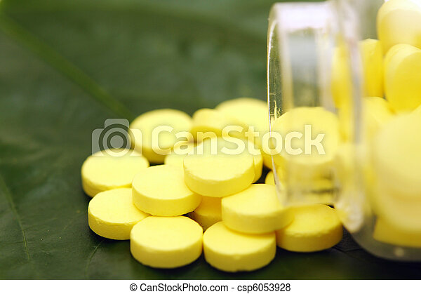yellow pill over a green leaf - csp6053928