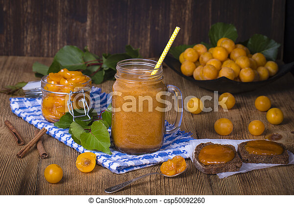 Yellow plum smoothie in glass, jam and ripe yellow plum on wooden table. Bio healthy food and drink - csp50092260