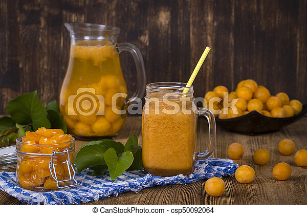 Yellow plum smoothie in glass, lemonade, jam and ripe yellow plum on wooden table. Bio healthy food and drink - csp50092064